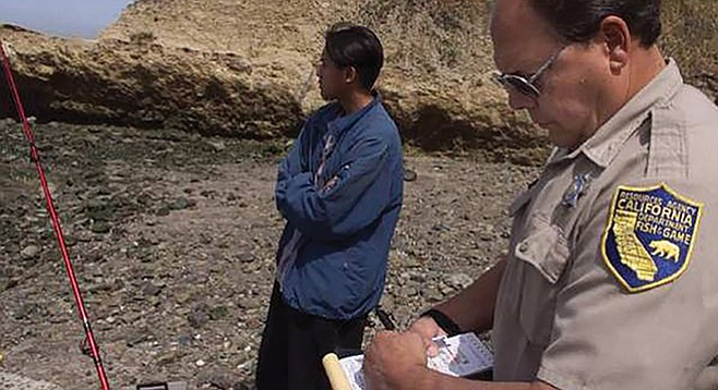 Department of Fish and Game warden Mike Buelna issues a citation to a 21-year-old angler for fishing with a blank license - Image by Robert Durell / Los Angeles Times