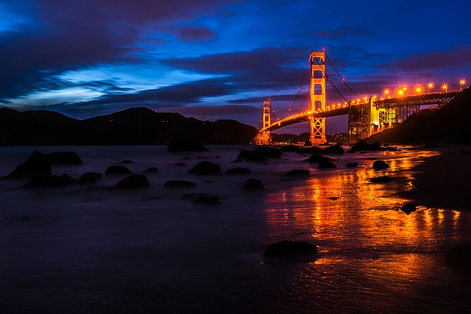 The Golden Gate Bridge viewed from Marshall's Beach on a dark stormy night.