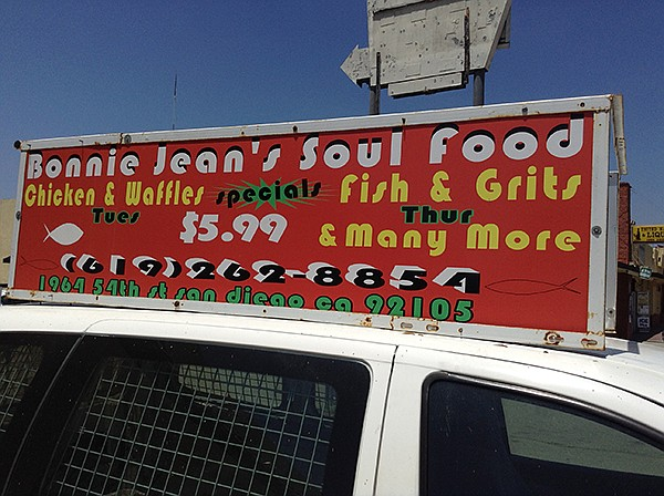 Sign on top of car in front of the restaurant
