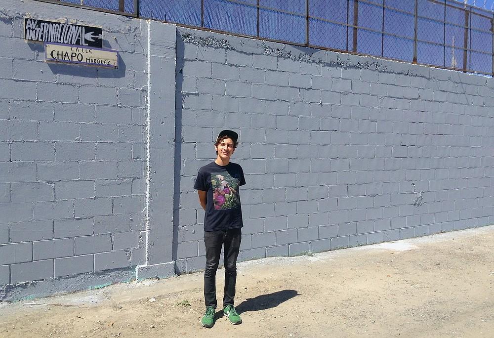 David Peña, standing next to the grey wall