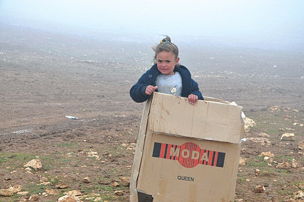 A cardboard box is treasure to a Yazidi girl, who saw the box that came packed with blankets as shelter from the cold atop Mount Sinjar.