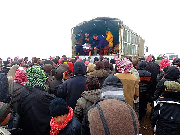 Portions of a Roads of Success shipment of supplies from San Diego to northern Iraq are offloaded atop Mount Sinjar.