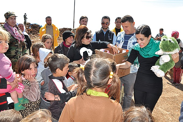 Yvette Isaac (center-left, wearing sunglasses) and Jacqueline Isaac (center-right) unpack toys, handing them to kids on Mount Sinjar