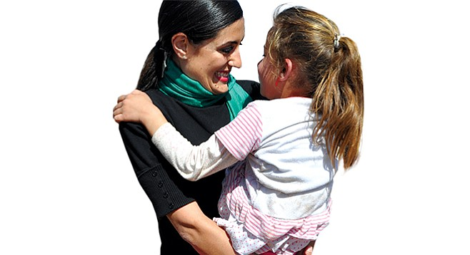 Jacqueline Isaac holds a Yazidi child on Mount Sinjar in Iraq