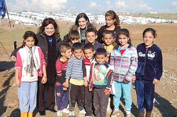 Yvette and Jacqueline Isaac with children from an internally displaced persons camp in Iraq. The camp can be seen in the background.