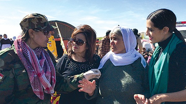 L-R: An unknown soldier of the Kurdish female fighting units explains to Yvette Isaac the challenges of protecting the Yazidis from ISIS; to Isaac's right are an Yazidi elder and daughter Jacqueline.