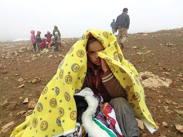 A Yazidi child takes refuge from the chilly weather atop Mount Sinjar beneath a blanket brought by the Isaacs.
