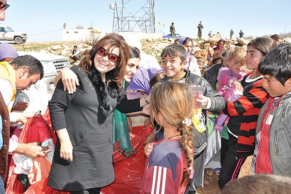 Yvette Isaac (center, wearing sunglasses) joins an elderly Yazidi woman in blessing gifts from Southern California