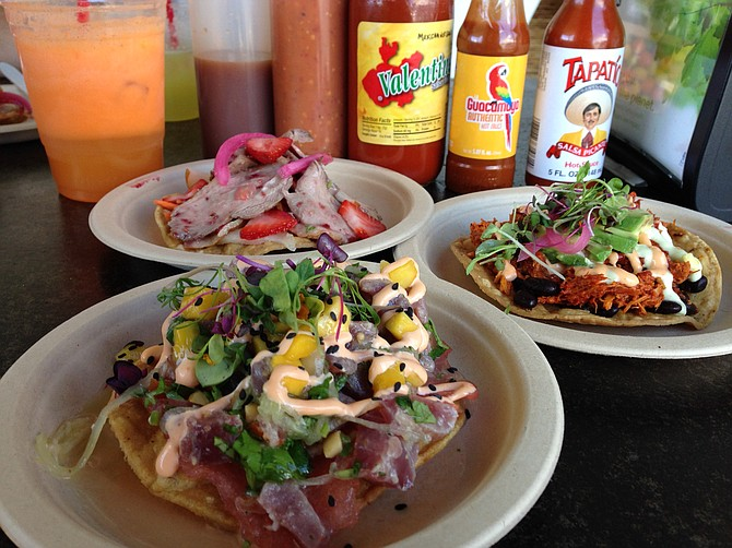 Hot sauces and fresh juice complement the Sandia (front), Pibil (right), and De la Pato (back) tostadas