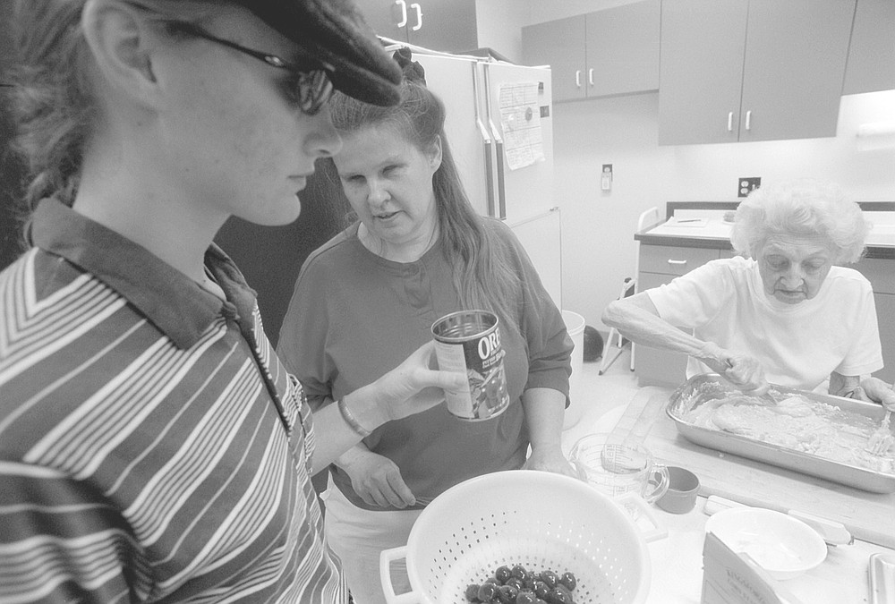 Linda (center) at cooking class. They taught the students how to prepare a spaghetti pie, salad, and spicy oatmeal cookies.