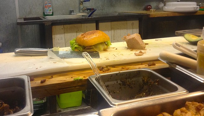 The sandwich in the kitchen, next to a big piece of maciza