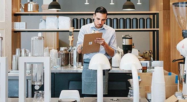 A barista takes notes at Copa Vida's East Village shop. Its Alpha Dominche Steampunk and Curtis Seraphim machines sit in the foreground.