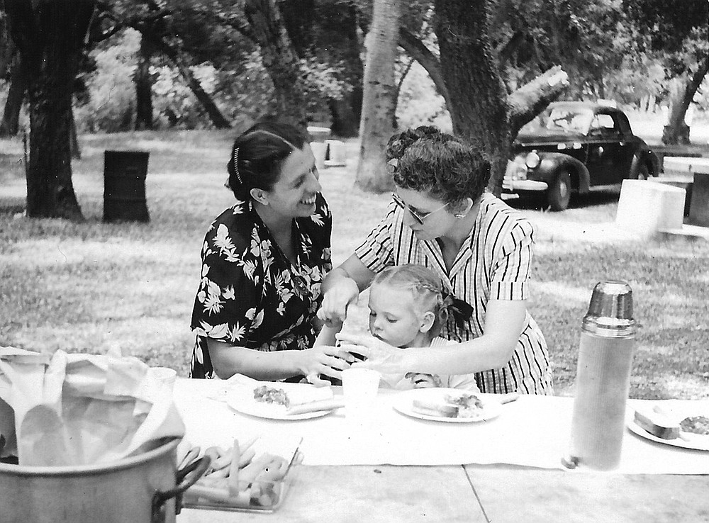 Lorraine Flippen, Judy, and Gladys, Live Oak Park, 1948. Lorraine's face is blurred with happiness, and Gladys looks efficient and capable, leaning over Judy to scoop something out of a jar.