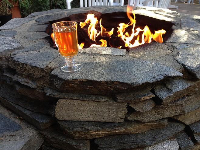 Warm apple cider beside a fire pit