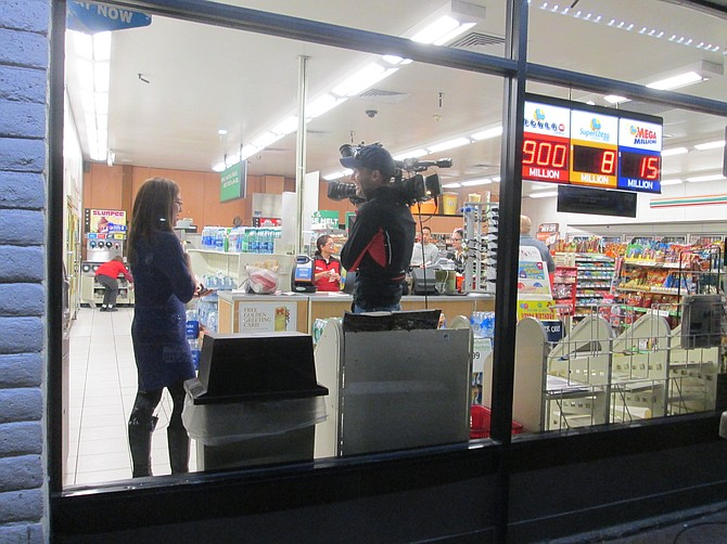 7/11 at 8th and Highland in National City with Powerball sign in the window, reporters from Channel 10 behind the glass.