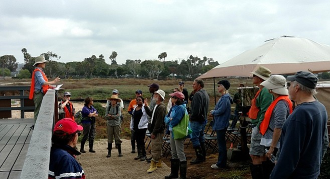 Visitors and volunteers gather before embarking on a morning marsh tour