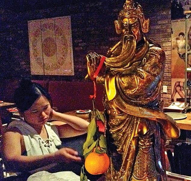 "Inside Lucky Liu's, Confucius and a gift of an orange, a very auspicious Chinese New Year symbol of wealth, luck, and gold. Added significance: ""Orange"" in Chinese sounds like the Chinese word for ""wealth."""