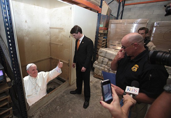 "Making an entrance: Pope Francis gives a happy thumbs up to United States diplomatic and immigration officials as he emerges from a cross-border tunnel into a San Ysidro Wal-Mart warehouse facility. ""It was very considerate of Mr. Pope to let us know exactly when and where he would be arriving,"" said ICE Commander Wally Brownout. ""But of course, we still had to take him into custody. He's a foreign national entering the United States through irregular channels, and the law is the law. When I explained that to him, he said that Pontius Pilate probably told himself the same thing. I have to admit, that stung a little."""