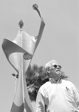 Julio Rodriguez, in front of a monument to the teachers of Tijuana, A car passes, stops, honks. Inside, two men wave and clap and call out the professor's name.