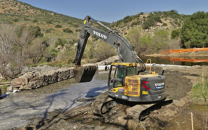 """The contractor used a loader to remove sediment from the dammed side of the island, switching to hand excavation """"within 10 feet of the dam to prevent damage by mechanized equipment."""""""