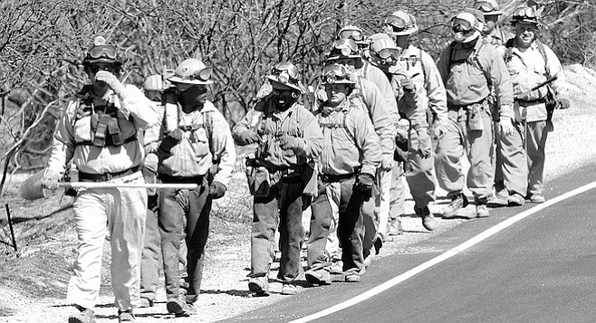 """CDF hand crew along Highway 94. """"The wind was blowing burning brands and embers down the hill and across Highway 94, where firefighters were trying to make another stand."""""""