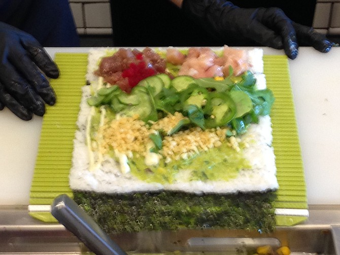A pre-roll sheet of nori and rice at Rolled Up, topped by ingredients.