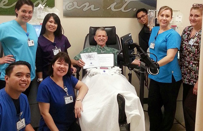 Gregory Kazwara (center) receives a certificate of appreciation from San Diego Blood Bank staff during his 50th gallon donation of blood.