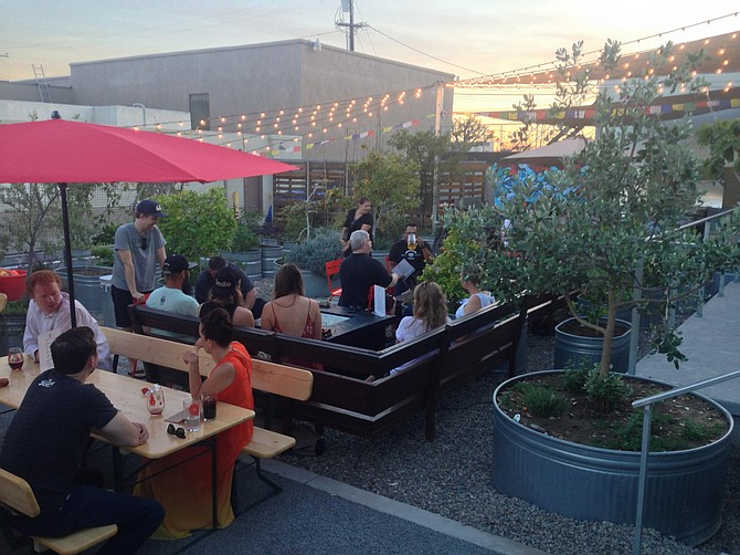 People drinking beer in a garden setting at North Park's new ChuckAlek Biergarten.