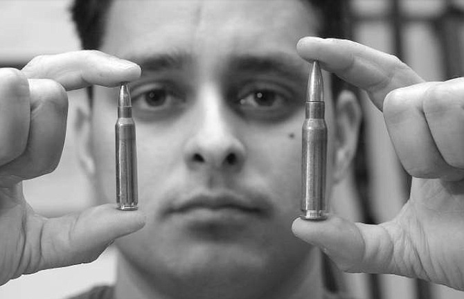 """James Montes, holding .223 and .308 caliber bullets. """"Gone is the day of trench warfare like in World War II and World War I. You are not having to pick guys off at 500 yards."""" - Image by Joe Klein"""