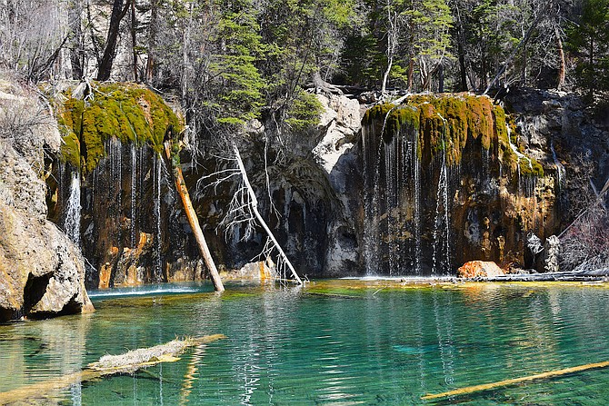 Hanging Lake, Glenwood Canyon, Colorado.  Had the pleasure of hiking to this awe-inspiring place while traveling to and from San Diego on the similarly awe-inspiring I-70.  The shoreline of the lake is made of dissolved limestone and its turquoise blue color is produced by carbon-based minerals deposited into the lake from a fault.