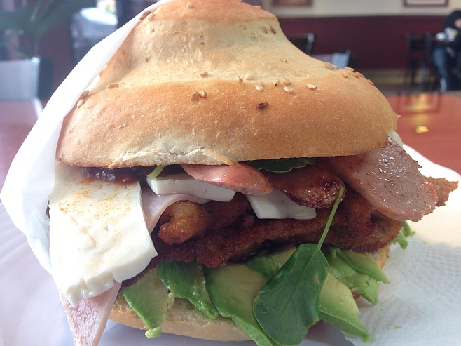 This Cubano Cemita features breaded pork, ham, and sausage with avocado, panela cheese, and papalo leaves.