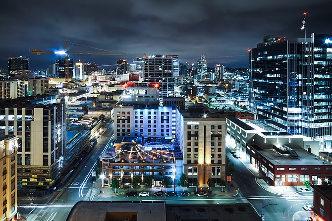 This long exposure photo, taken from the Altitude Sky Lounge in downtown San Diego, shows the skyline from the famous Gaslamp District, while an airplane passes in the background and traffic moves on the ground. Photo by Andrew Barnhart (Email: andrew.barnhart@gmail.com, Instagram: @oncloudmine)