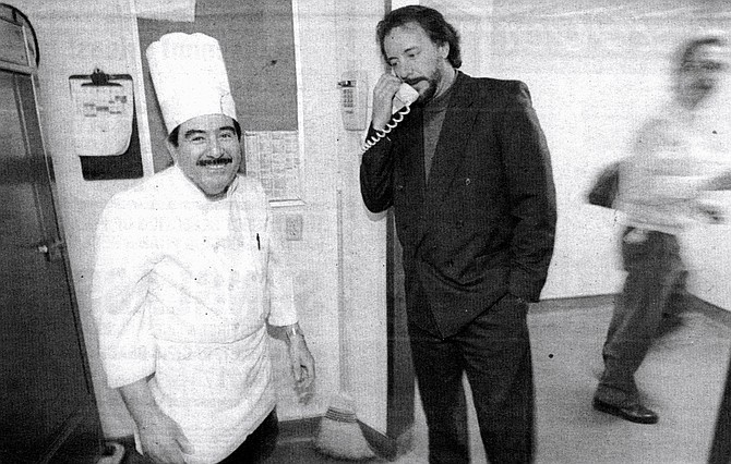 "Chef William Rivera (left) and Jef Eatchel (center) on phone.  ""For a lot of these people, this is their main meal, and it's usually two: one before or after your shift, one on your break."" - Image by Sandy Huffaker, Jr."