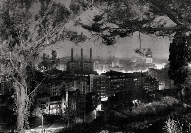 Barcelona Through the Trees, 1982. It's night. Seen from a high vantage point, through a framing wreath of trees, the city looks as if it's on fire.  - Image by Philipp Scholz Rittermann