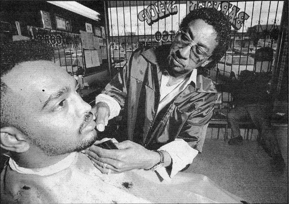 "Bob Coleman, Mt. Sinai Barbershop;  ""That's my brother there. He was a minister, and after he died, his customers   keep coming."""