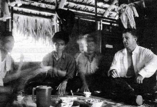"Dinner in Montagnard village (author far right). ""Montagnard, he like pepper hot. Use chickenshit. Fertilize. Make pepper very hot."""