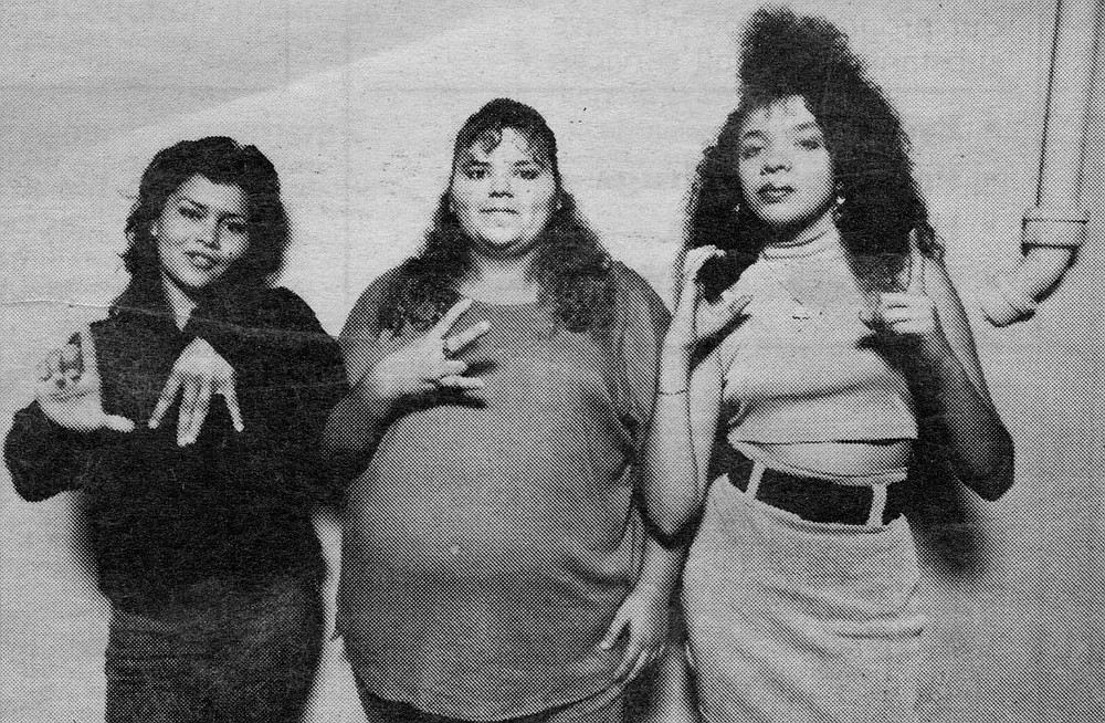 "Bam-Bam, Cookie, and Joker, demonstrating hand signals ""Lomas,"" ""26,"" ""Chicas #1."" Joker testifies that she learned about the shooting from the homeboys hanging out at Dave's Market at 26th and Broadway."
