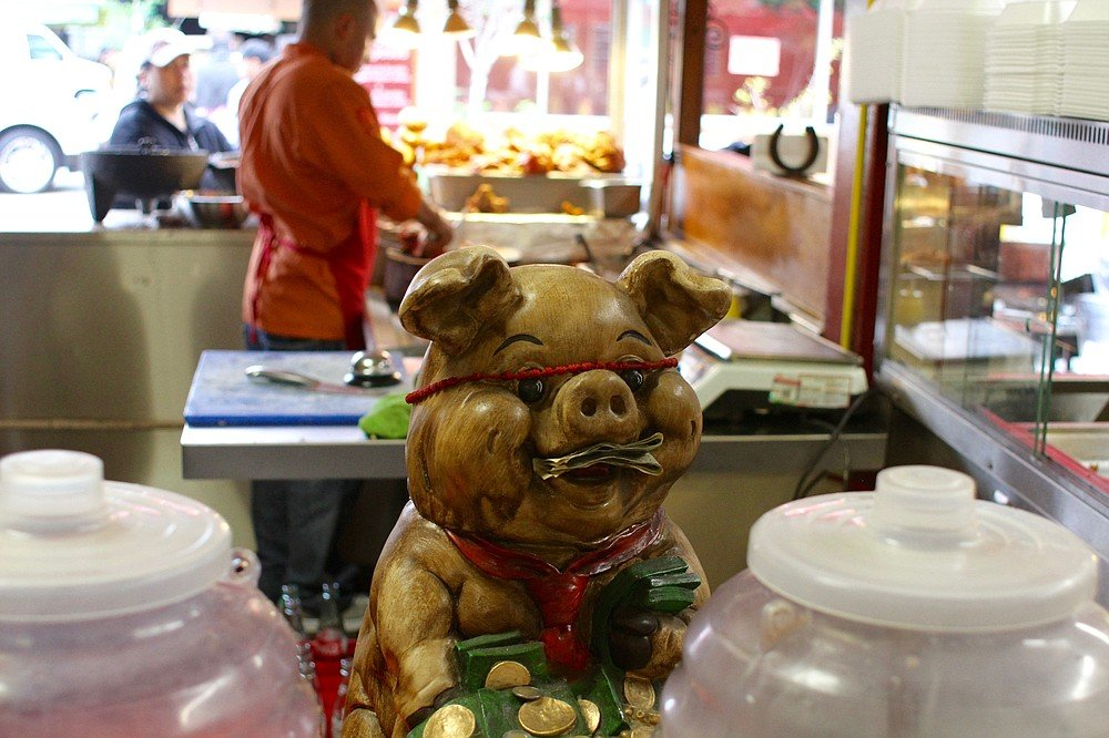 Giving change to the pig for good luck (and then the cook's tip jar)