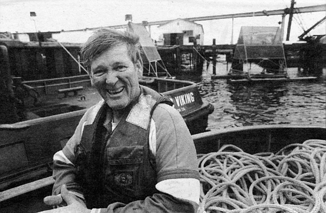 Frank Roche.  I am directed to the stern with Gary and Frank. Three sailors wearing life jackets and helmets, holding automatic weapons on the ready, guard us.