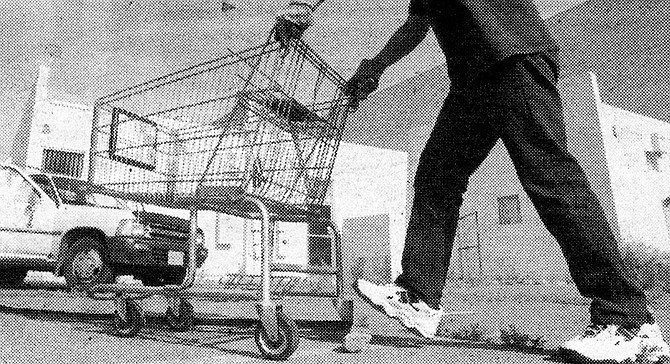 Eddy tells me this man separates the carts by store for Eddy. In return, Eddy brings him cheeseburgers. - Image by Sandy Huffaker, Jr.