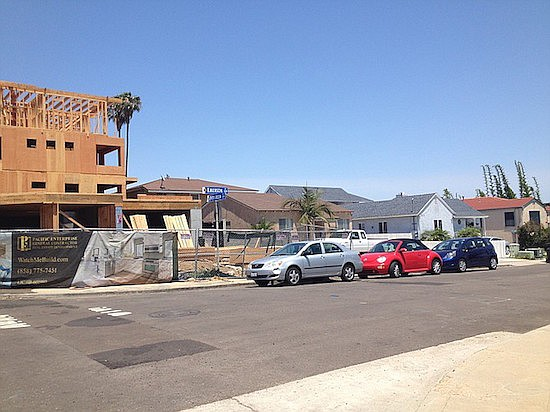 """The view from across Emerson Street — second duplex hasn't reached second-story level yet. """"Pacific Enterprises...WatchMeBuild,"""" reads the construction banner"""