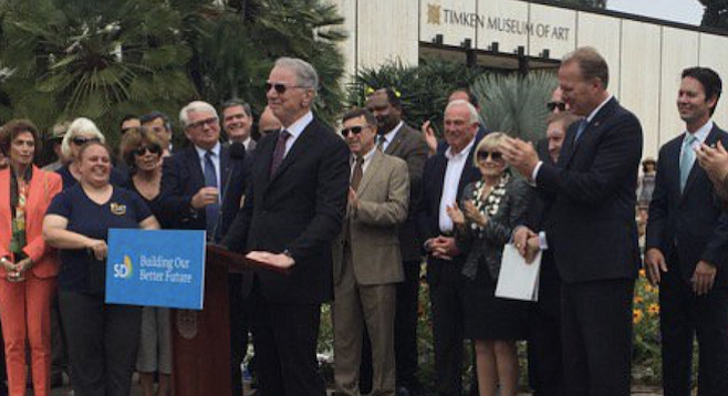 June 30, 2016, in Balboa Park: Irwin Jacobs at the lectern, Faulconer applauding behind him, former mayor Jerry Sanders between (without the tie)
