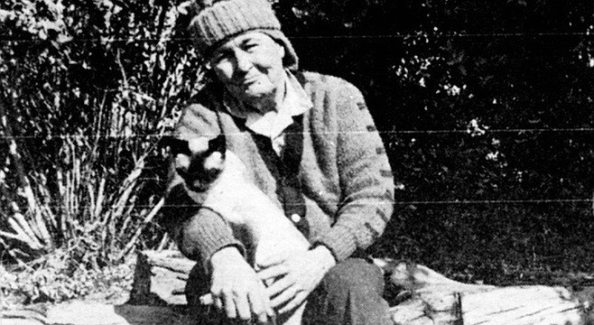 """Audrey and her pet cat. She was muttering something about """"luggin' these damn small saws like that."""" She finished this tree, too, and handed me back the saw."""