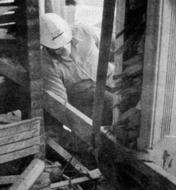 A workerman disassembles the original hotel. The building was demolished and every salvageable piece of brick, mortar, and bric-a-brac carefully cataloged and stored.