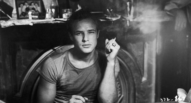 Marlon Brando grabbing a smoke between takes on the set of A Streetcar Named Desire.