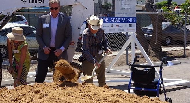 Robert Bettinger (right) set aside his walker to throw a shovelful of dirt
