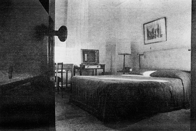 The center of the room is occupied by a queen-size box spring and mattress. mounted on a metal frame.