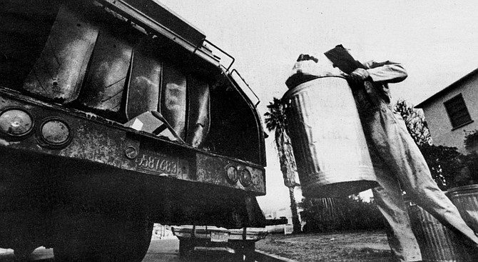 Trash man taking cans to garbage truck - Image by Jim Coit