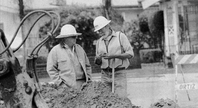 Larry Pierson (left), archeologist, and George Kennedy, paleontologist, examine a rock specimen