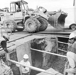 Mark Breshears (in front-end loader) lifts metal plates from new manhole; Genaro Tapia (in hole) sets speed-shoring; above hole, Joaquin Suarez (left), Don Gingrich (right)